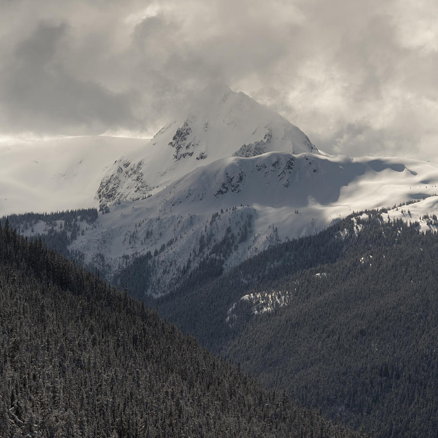 Clouds over snow covered mountains Photograph by Fotosearch