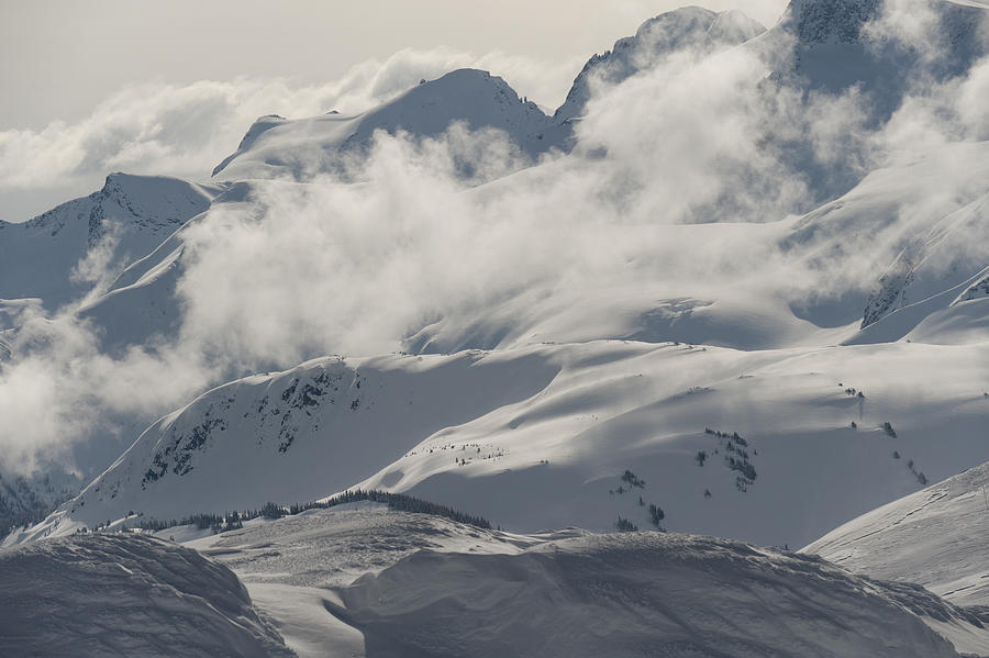 Clouds over snowcapped mountains Photograph by Fotosearch