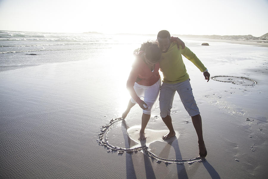 Couple drawing heart in sand on beach Photograph by Resolution Productions