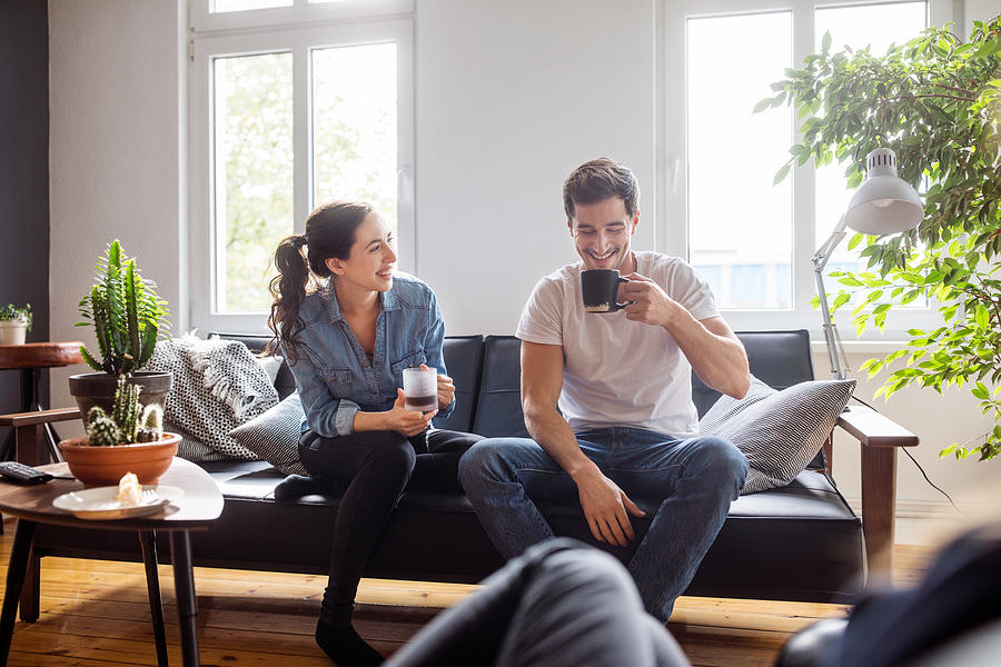 Couple having coffee together in living room Photograph by Luis Alvarez