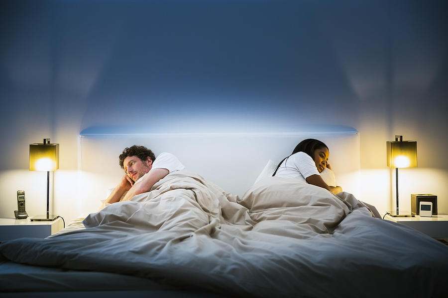 Couple ignoring each other on bed Photograph by Portra