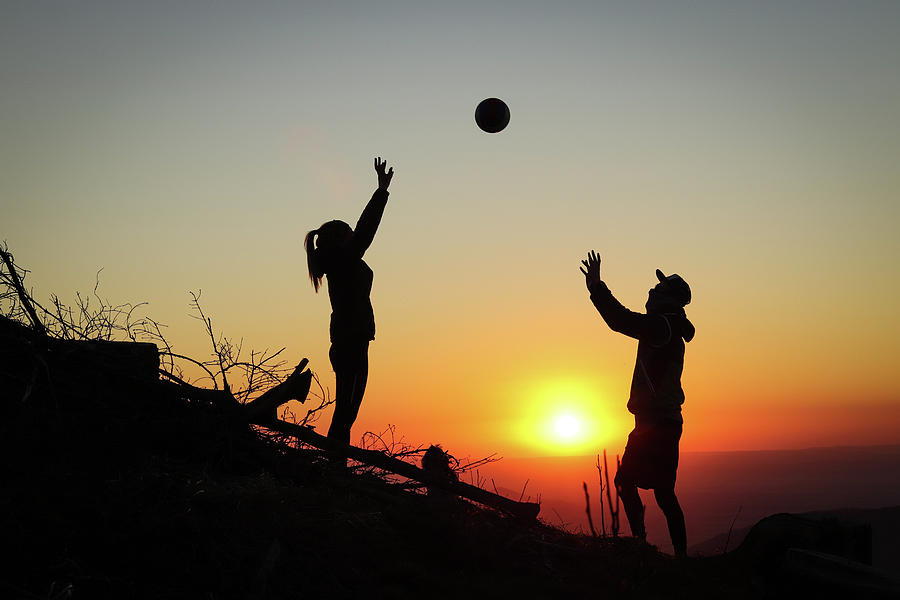 Couple Is Playing Volleyball At Sunset Photograph