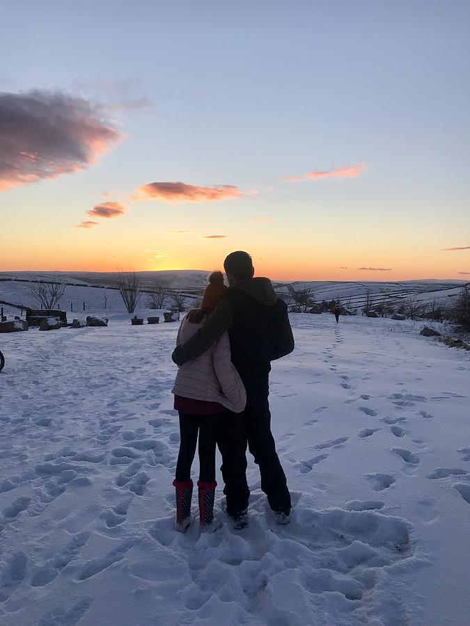 Couple looking at sunset in snow Photograph by Heidi Coppock-Beard