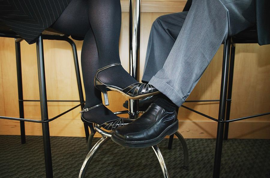 Couple Playing Footsie Under the Table Photograph by Kelly Redinger