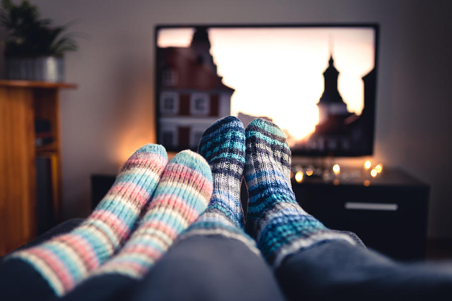 Couple with socks and woolen stockings watching movies or series on tv in winter. Woman and man sitting or lying together on sofa couch in home living room using online streaming service. Photograph by Tero Vesalainen