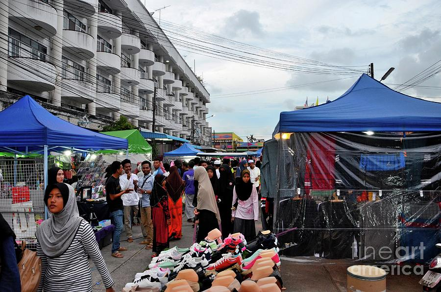 Crowds of people hang around outdoor street market shops and food stalls Pattani Thailand by Imran Ahmed