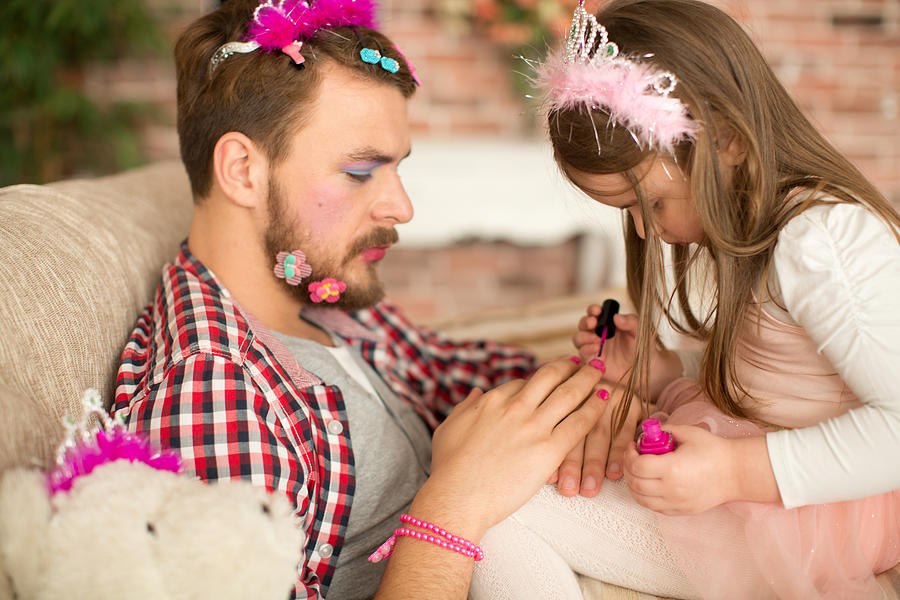 Cute daughter making up her father. Photograph by Svetikd