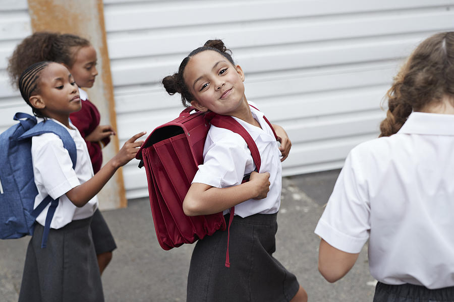 Cute schoolgirl looking to camera while walking from school with friends Photograph by Klaus Vedfelt