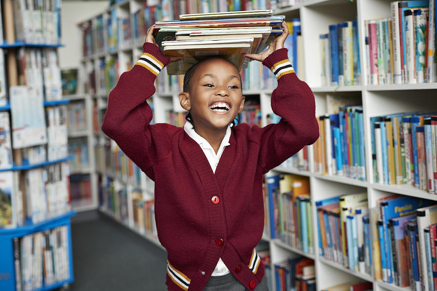 Cute schoolgirl smiling & balancing stack of books on the head at library Photograph by Klaus Vedfelt
