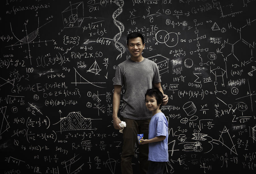 Dad and son in front of math covered chalkboard Photograph by Justin Lewis