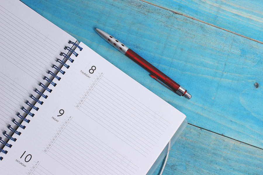 Directly Above Shot Of Spiral Diary And Pen On Wooden Table Photograph by Vesna Boskovic / EyeEm
