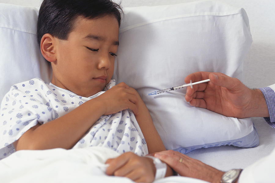 Doctor in hospital giving boy (5-6) injection in arm Photograph by Keith Brofsky