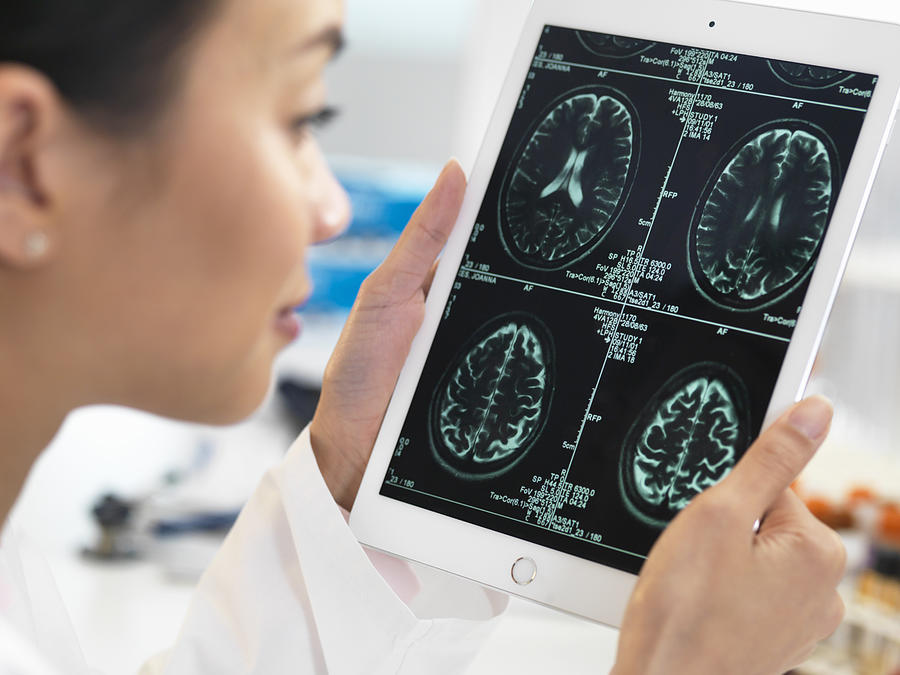 Doctor viewing CT scan result of brain on digital tablet for abnormalities Photograph by Andrew Brookes