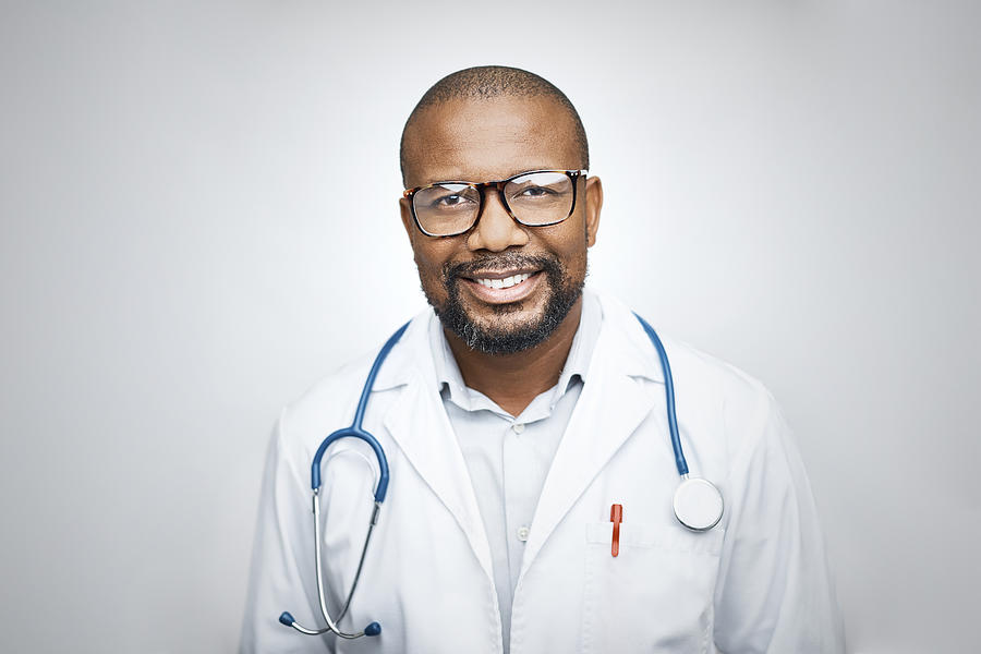 Doctor wearing eyeglasses on white background Photograph by Morsa Images