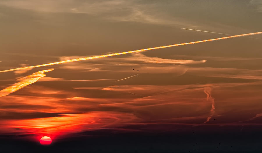 Dramatic sky at sunrise sun at the left Photograph by Jean-Marc PAYET