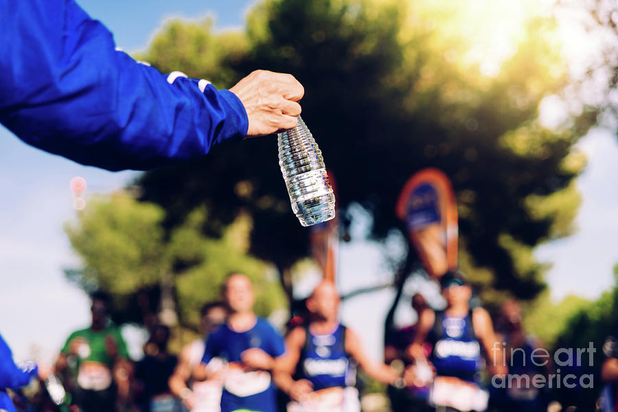 Drinking water is important when we exercise like running to avoid becoming dehydrated. by Joaquin Corbalan