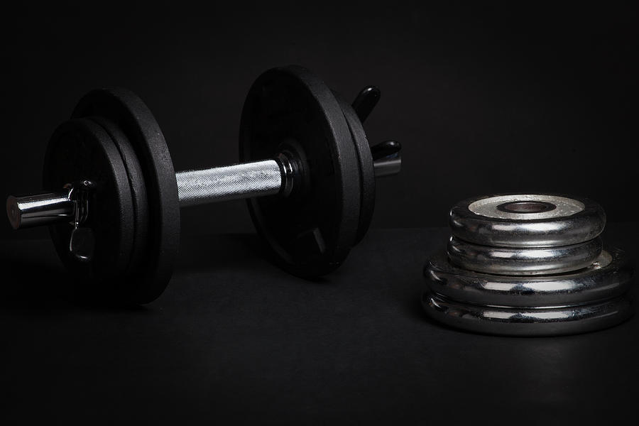 Dumbbell And Barbell Discs For Workout On Black Background Photograph