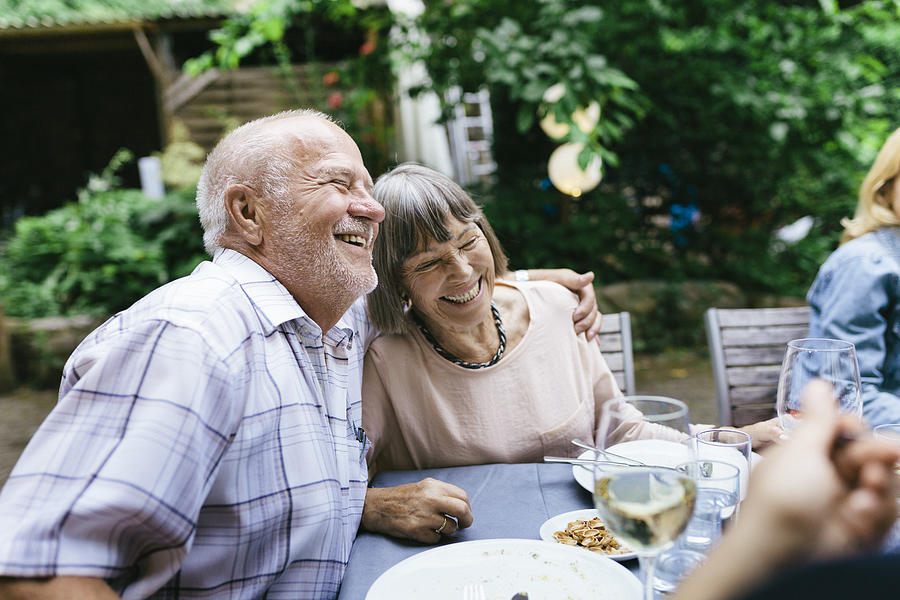 Elderly Couple Enjoying Outdoor Meal With Family Photograph by Hinterhaus Productions