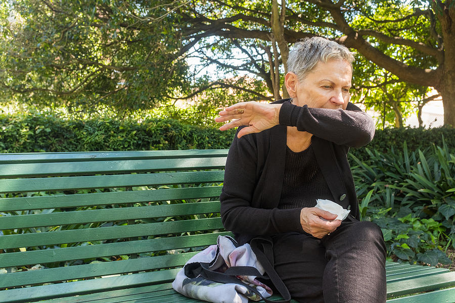 Elderly woman coughing into elbow and holding tissue outdoors Photograph by Natalie_board