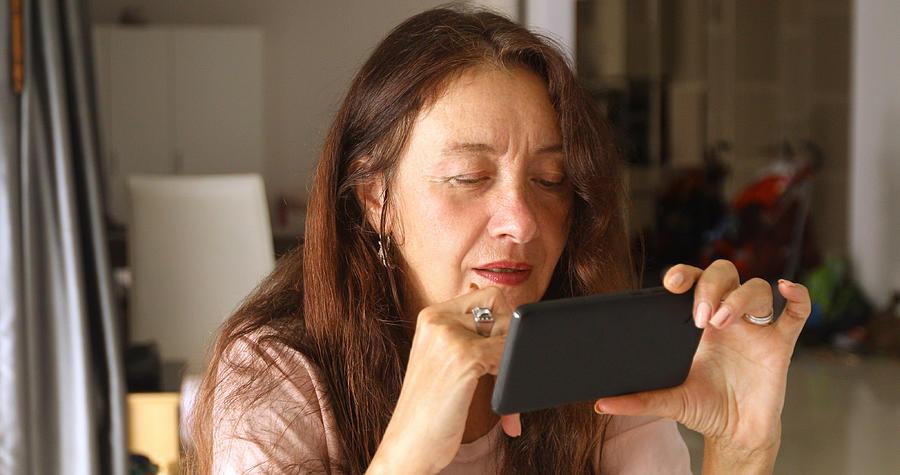Elderly woman using smartphone Photograph by Demkat