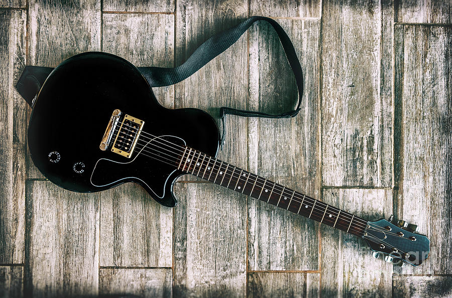 electric guitar grunge look studio shot up view on wooden background by Luca Lorenzelli