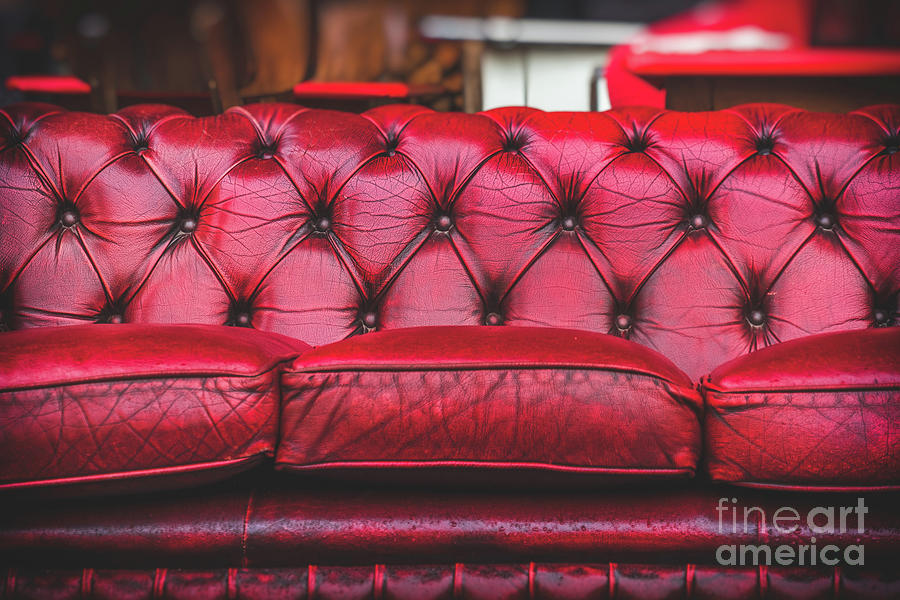 empty red sofa in cosy lounge room old-fashioned vintage closeup by Luca Lorenzelli