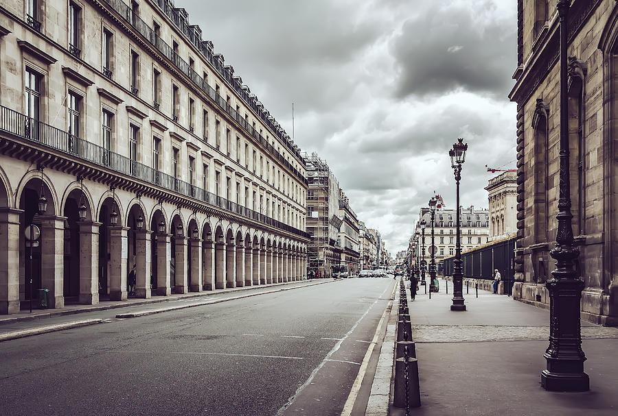 Empty Rue De Rivoli street against dramatic sky in Paris Photograph by Kolderal