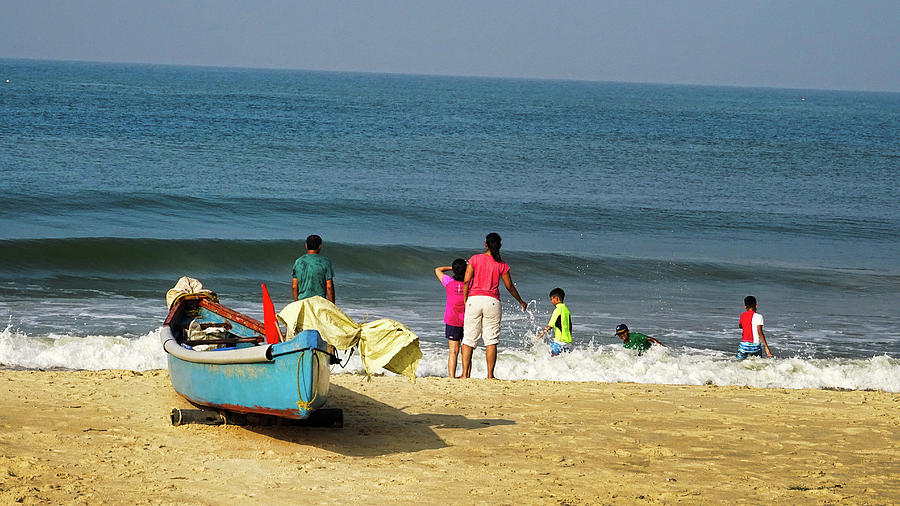 Families enjoy the time on the beach in India by Santosh Puthran