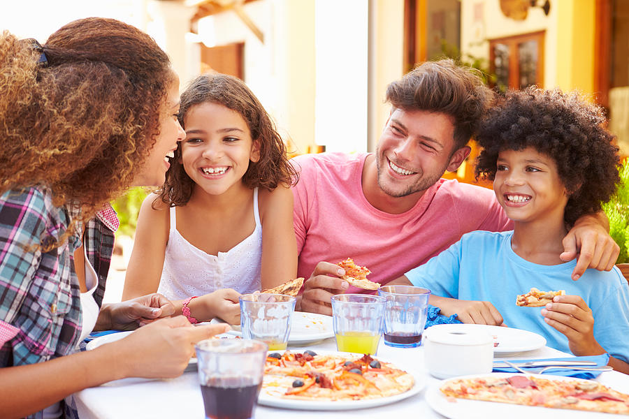 Family gathered at an outdoor restaurant to share a meal Photograph by Monkeybusinessimages