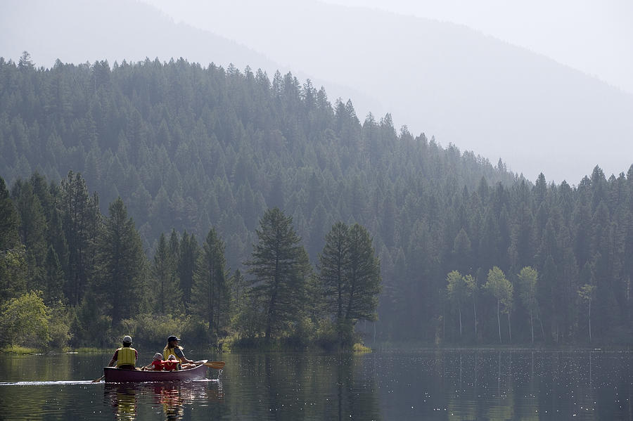 Family in canoe Photograph by Comstock Images