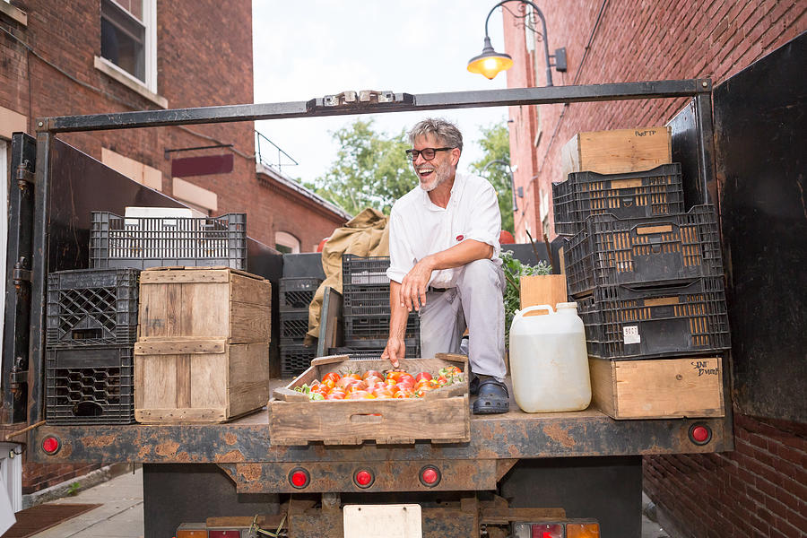 Farmer unloading crates of organic tomatoes outside grocery store Photograph by Heshphoto