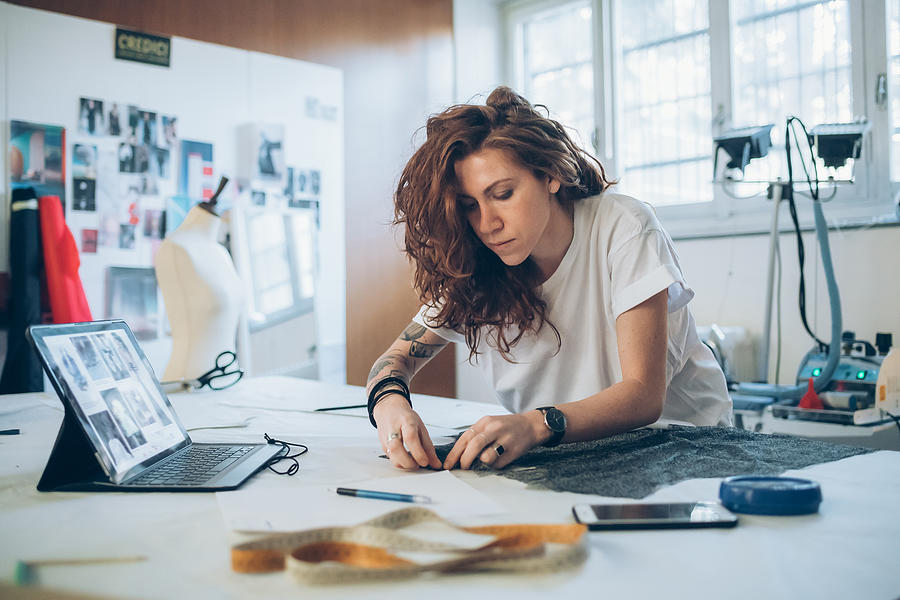 Fashion designer pinning fabric cutouts Photograph by Eugenio Marongiu