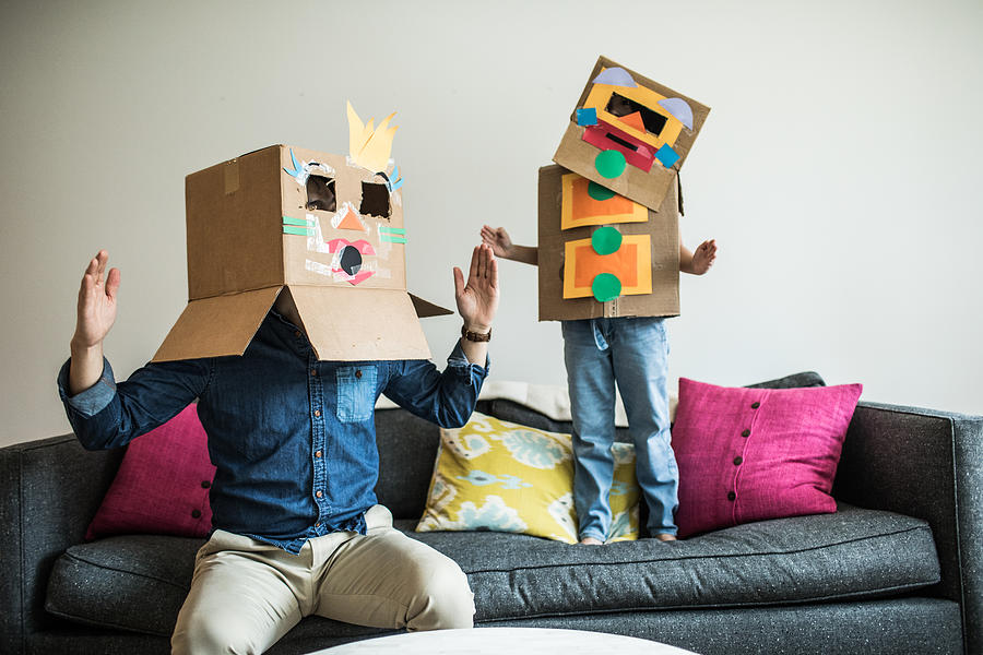 Father and daughter wearing robot costumes at home Photograph by MoMo Productions