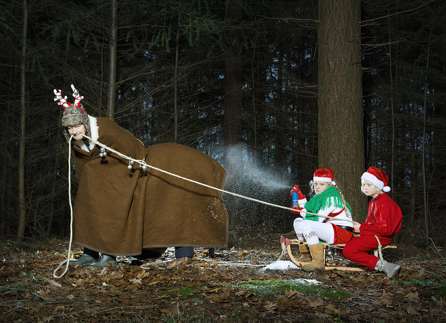 Father disguised as reindeer pulling sleigh with children in Santa costume Photograph by Mischa Keijser