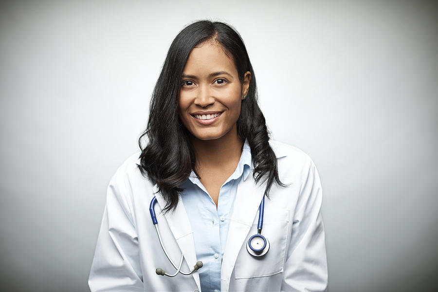 Female doctor smiling over white background Photograph by Morsa Images