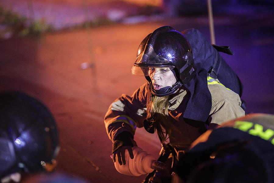 Female firefighter helping injured Photograph by Vm