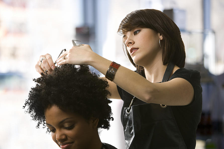 Female hairdresser trimming a young womans hair Photograph by Rubberball