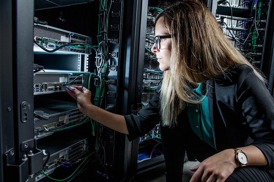 Female IT Engineer Working in Server Room Photograph by CasarsaGuru