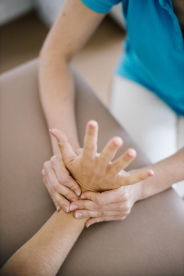 Female physiotherapist giving patient a hand massage, close up Photograph by Westend61