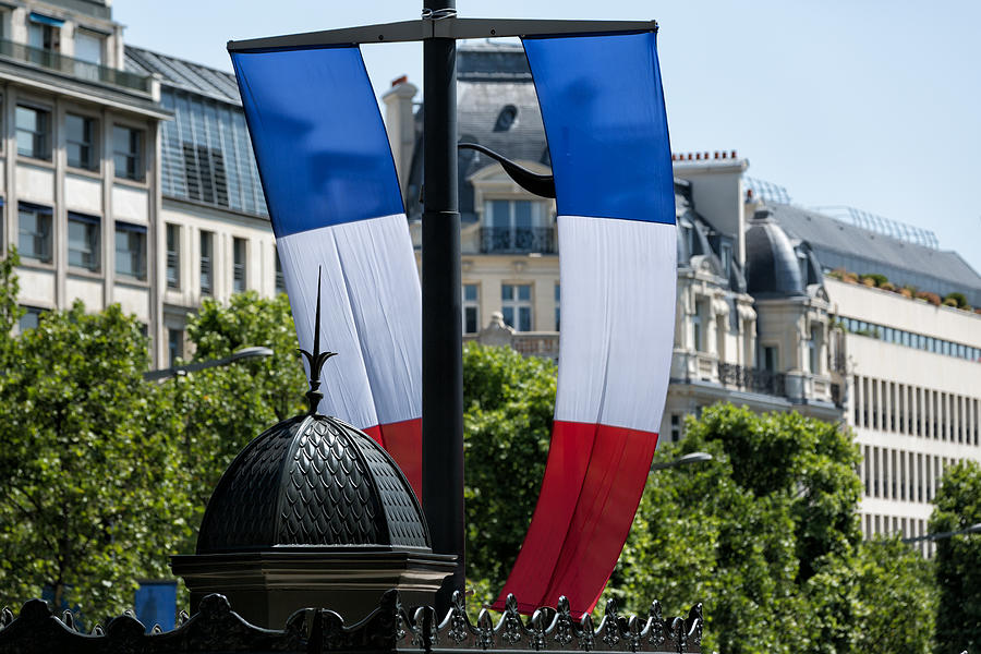 French flag and typical Parisian rooftops in Champs-Elysées. Photograph by Jean-Marc PAYET