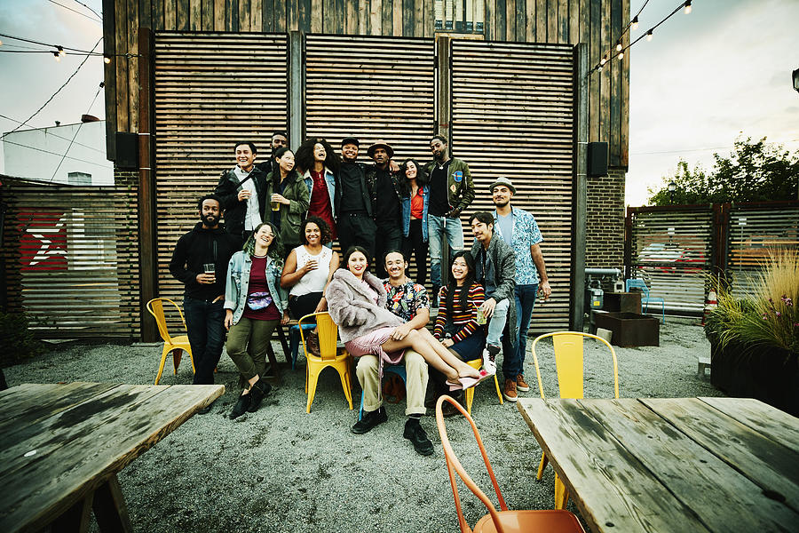 Friends posing for group photo during party at outdoor restaurant Photograph by Thomas Barwick