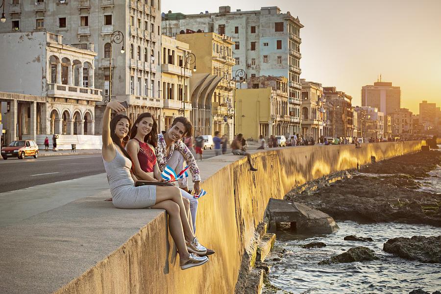 Friends taking selfie on retaining wall in Havana Photograph by Xavierarnau