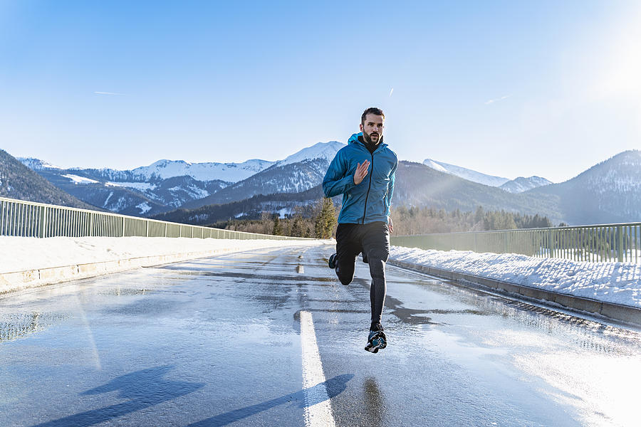 Germany, Bavaria, sportive man running on a road in winter Photograph by Westend61