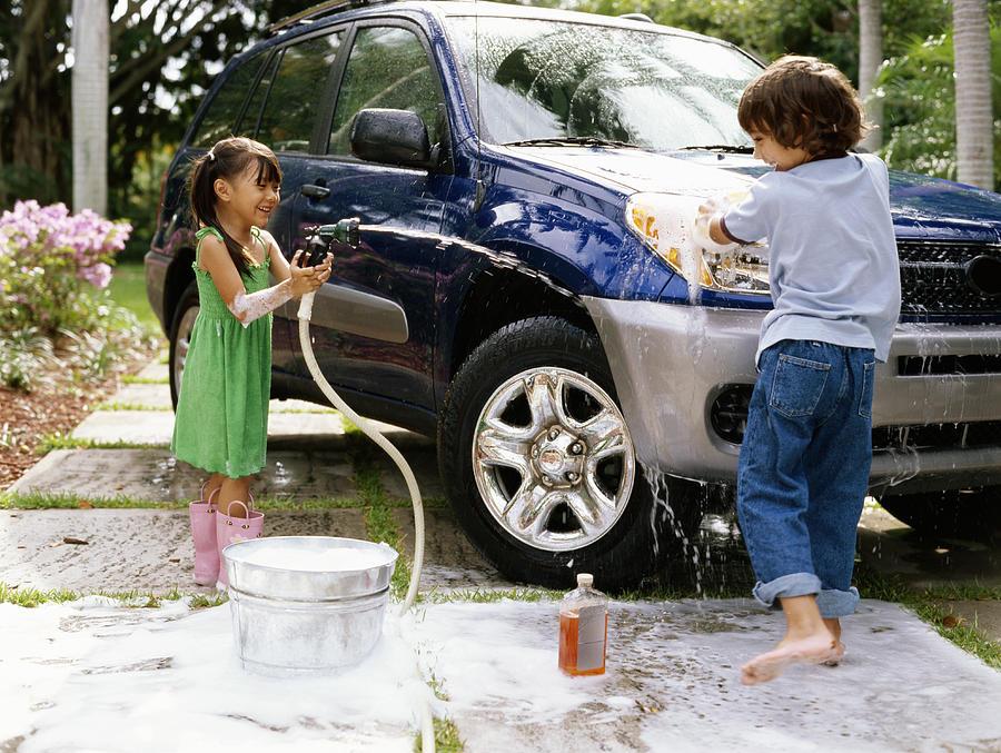 Girl (4-6) aiming hose at boy (5-7) washing car on driveway, smiling Photograph by Kraig Scarbinsky