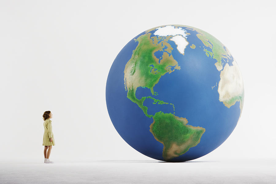 Girl (8-9) standing in empty white room, looking at huge globe (digital enhancement) Photograph by Martin Barraud