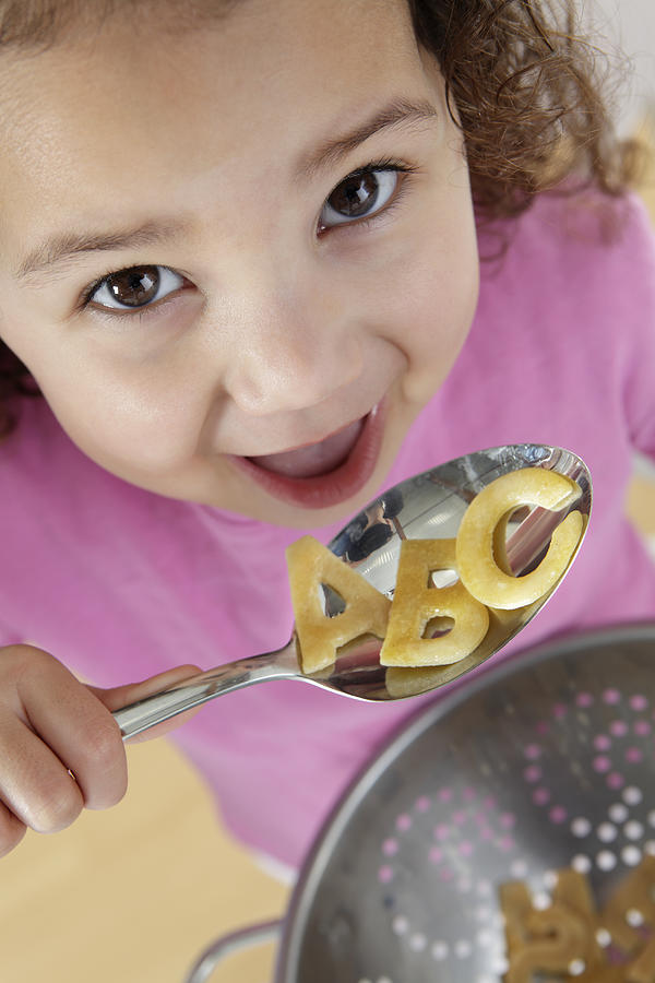 Girl eating alphabet pasta Photograph by Peter Cade