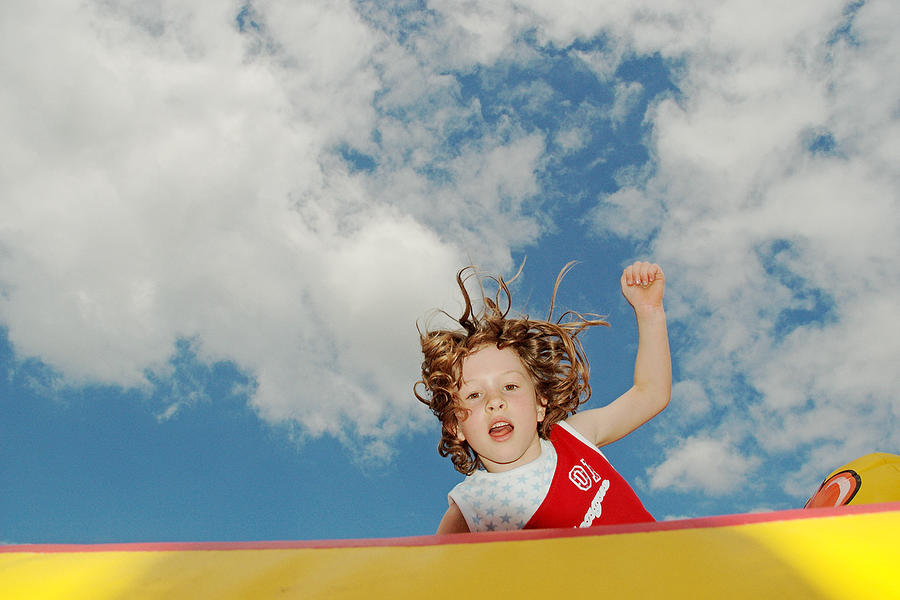 Girl jumping on bouncy castle Photograph by Image Source