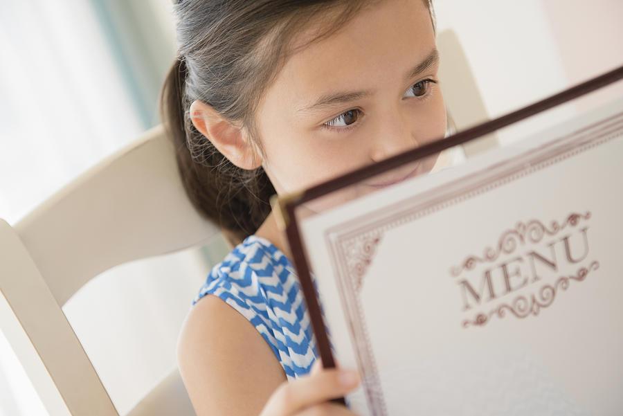Girl reading menu in restaurant Photograph by JGI/Jamie Grill