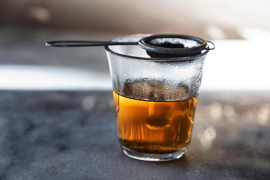 Glass filled with hot tea from a strainer filled with tea leaves on top on a gray marble tabletop. Photograph by Emreturanphoto