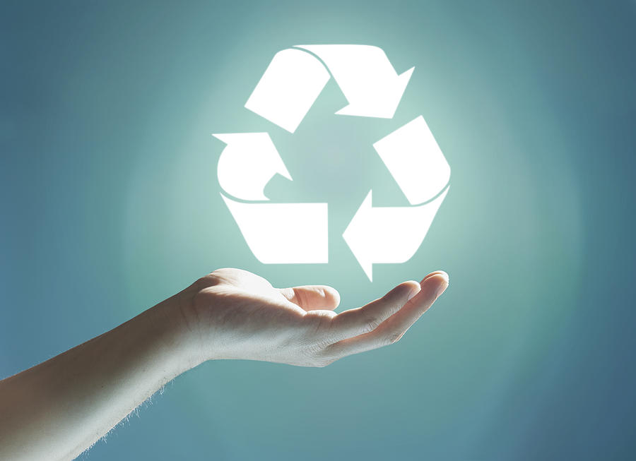 Glowing recycling sign floating above hand Photograph by Paper Boat Creative
